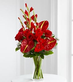 Sympathy Flowers - FTD We Fondly Remember Bouquet - The FTD We Fondly Remember Bouquet is an expression of endless love in this time of loss and grief. Whether sending this bouquet to honor the deceased at their final service or to comfort a friend or family member for their loss, this arrangement of rich red roses, gladiolus and anthurium, offset by lush greens and arriving in a clear glass vase, will convey your warmest sentiments with each exquisite bloom. Approximately 27H x 15W,.