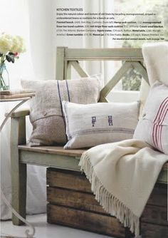 Green painted rustic entry bench with wooden crate underneath.  I also like the grain sack pillows.