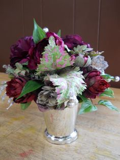 Faux flowers are elegantly arranged in this julep cup. (Flowers designed by Seven Sisters Florist) www.sevensistersflorist.com