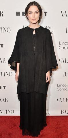 """Keira Knightley graced the red carpet at """"An Evening Honoring Valentino"""" in a rather refined look, courtesy of Valentino Couture, in which she layered a black suede caped coat over a long black gown."""
