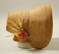 Straw bonnet 19th century, American or European - simple decoration, just sprigs of wheat and flowers - in the Metropolitan Museum of Art costume collections.