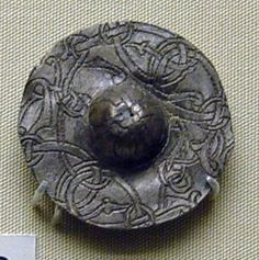 """""""Disc-brooch; lead alloy; bossed centre bearing interlaced cross; punched decoration in Urnes style of looping fronds and ribbons; pin with applied hinge and catchplates on back; catch is partly flattened. Culture/period: viking Date: 1026-1075"""" (quote) © Trustees of the British Museum via britishmuseum.org"""