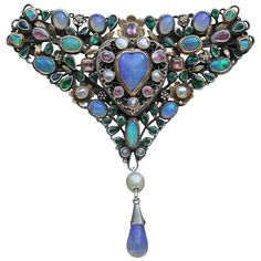 Triangular Corsage Brooch 'Loves Garland' by Arthur Gaskin and his wife Georgie is a fine example of their romantic Arts and Crafts jewelry. Signed 'G' verso. Original fitted case. Silver, gold, opal, pink tourmaline, blister pearl and emerald paste.