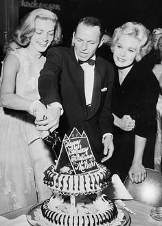 "Frank Sinatra & Kim Novak help Lauren Bacall cut into her birthday cake, which reads ""Happy Birthday Betty Queen Mother,"""