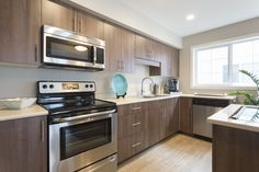 Modern finishes, stainless steel appliances and oversized windows create the perfect kitchen! Pocket Neighborhood, Healthy Exercise, Oak Park, Stylish Kitchen, Beautiful Park, Stainless Steel Appliances, Amber, Kitchens, Kitchen Cabinets