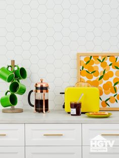 Bright accessories, fruit-themed art and green mugs decorate a white hexagon tiled backsplash. See more on HGTV.com.