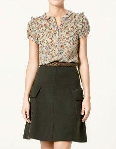 Flower blouse, belt, and black skirt.