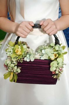 Green cymbidium orchids and hydrangeas decorate this purple flower girl basket, full of light hydrangea petals.