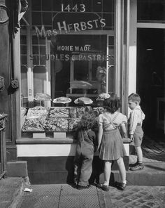"""""""Three children stand and look in the window of Mrs Herbst's bakery. 1960."""" (Getty)"""