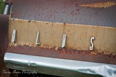 Close up of old Oldsmobile logo on rusty car.