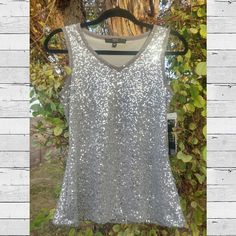 Beautiful silver sequined tank top NWT, silver sequined tank top. Material under sequins is a mesh, very different. It's also fully lined. Bought to sit in my closet apparently, since I never had an occasion to wear it!! Size small.   #sequin #sequins #sequined #silversequins #sequintop #alexmarie Alex Marie Tops Tank Tops