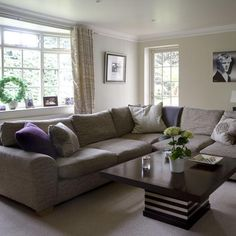 A corner modular sofa zones the living area and creates a cosy place to relax - perfect for sitting around with friends and family. Purple cushions add colourful accents and go well with the grey sofa, while statement furniture like the coffee table adds
