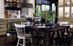 Ein großer Esstisch aus dunklem Holz mit unterschiedlichen Stühlen in der Mitte einer modernen, schwedischen Küche.
