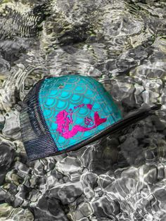 Mermaid scale snapback design with pink or burgundy embroidered mermaid blowing kisses of Hawaiian islands. Grey bill and back mesh.