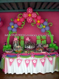 Mesa decorada con arco de globos para una comunión