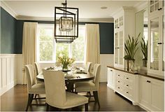 dark teal walls with white board and batten and large industrial light over table...