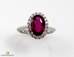 AGL certified not heat 2.51ct oval ruby surrounded by over .25cts of round brilliant cut diamonds. Set in 18kt white gold