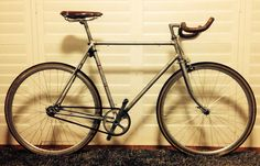 My Gentleman's Racer. Drop bullhorns, leather saddle and bars. Gum wall tyres. Classic bombproof 36 spoke triple cross wheels. It goes like stink. Fixed.