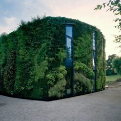 The lush facade, designed to benefit the vegetation, features a semi-circular form that follows the path of the sun.
