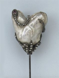 AN ANTIQUE NATURAL PEARL AND DIAMOND HAT PIN  The large heart-shaped pearl set to a rose-cut diamond set flower mount, a diamond set snake with ruby set head twisted around the top, 19th Century, pearl imperfect. Valued at 3,500 USD