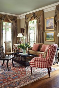 Sophisticated Colors with Red Accents...This living room's sophisticated color scheme was inspired by the serapi rug underfoot. A red-and-white gingham fabric from Cowtan & Tout covers the Lee Jofa chair. Gold and toffee furnishings highlight the rug's blue tones.  Traditional Home