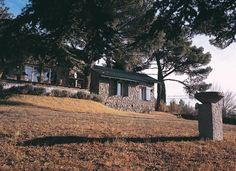 La piedra de una cantera de la zona, enriquecida con la textura de la madera, definió el estilo de la fachada y los interiores de esta casa.