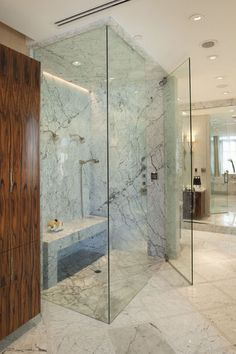 Around the corner in the master bathroom, the Bianco Carrera marble continues on into the shower, with an all-marble bench against one wall.  Herzlinger decided to use pau ferro for the cabinetry in the bathroom — an exotic wood that's found in Brazil and Bolivia. Most often used in guitar making, pau ferro has a unique grain and coloration that can also be used in furniture.