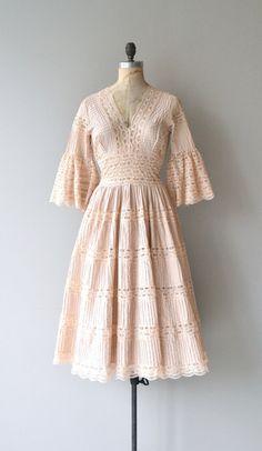 Vintage 1950s pale blush pintucked cotton and lace dress with wrap style bust, fitted waist, full skirt, bell elbow sleeves and metal back zipper. ---