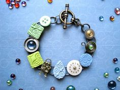 Mixed media stamped polymer clay bracelet with upcycled watch parts - Ocean Pastels.