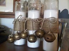 The choice: buy at pottery barn, or DIY!  Buy some of the tall candles like seen here (I see them even in grocery stores), apply glue to center section. Wind twine and end with a bow.  Tie jingle bells onto ends of twine.  Three for about $8.    Pottery Barn inspired candles - christmas