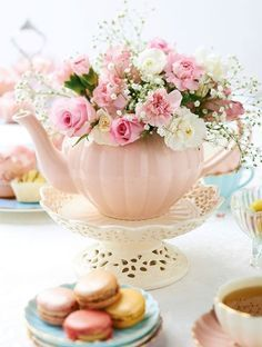 Sweet pink teapot with floral arrangement, perfect for tea party table decor.