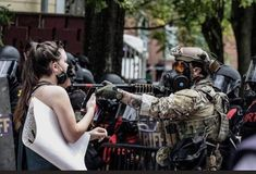 An unidentified officer points his firearm at an unarmed white woman during protests against police brutality, Columbia, South Carolina, May 31, 2020. Photo credit: Crush Rush