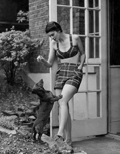 the50s:    Clothing Beach. Model wears checked shorts and bra top. Dachshund dog jumping up for food. July 1950.