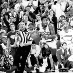 Black and white photo of University of Oregon basketball player Anthony Taylor dribbling the ball up the court in a game played during the 1987-88 season. ©University of Oregon Libraries - Special Collections and University Archives