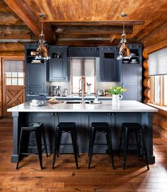 A bold contrast of grey cabinets against the natural wood gives this Canadian cabin an unexpected softness. The cabinets also hide all the appliances, making them both beautiful and functional.