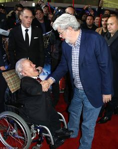 Fancy seeing you here! R2-D2 actor Kenny Baker (left) shook hands with filmmaker George