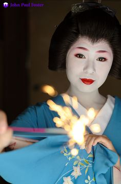 Yukako, a geisha in Gion Kobu in Kyoto, holds a sparkler in the heat of summer