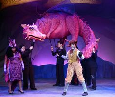 Dragon from Shrek the Musical | gdtheatricals.com | A large-scale puppet operated by 4-6 puppeteers, Shrek's Dragon is 23-foot long with fully-articulated wings, eyes and mouth. Red lipstick and large eyelashes unmistakably convey Dragon's feminine side.