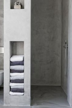 Concrete shower and built-in shelves for towels.