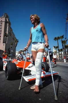 Retired British Formula One driver James Hunt arrives at the USA-West Grand Prix in spite of a massive leg cast (the result of a skiing accident), Long Beach, California, United States, 1980, photograph by Rainer W. Schlegelmilch.