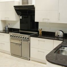 The Falcon Deluxe 900 Induction Range Cooker featured in stainless steel against contemporary white cupboards provide a modern style kitchen.