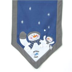 """Detroit Lions Snowman Table Runner by SC Sports. $29.95. Detroit Lions Snowman Table Runner. Polyester and fleece. Detroit Lions. 100% Polyester blend. SC Sports 72""""x15"""" Snowman Table Runner. Each runner features embroidered stars, parent and child snowman on each end, dressed in each team's official team colors and logo."""