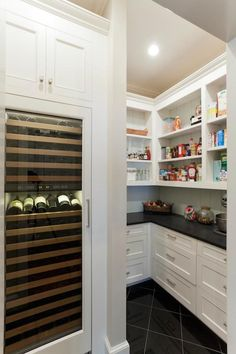Stunning pantry with tall, integrated glass front, wine fridge below built-in cabinets accented with nickel drawer pulls. White cabinets below sleek black counter alongside tongue and groove backsplash with open shelving