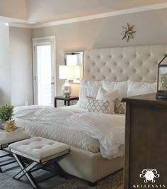 White Tufted Ottoman Benches with Mirrored Legs in front of Bed- Kelley Nan: Master Bedroom Update- Calming White and neutral master bedroom with tufted ottoman stools, Pottery Barn Tall Lorraine Headboard, Diamond linen quilt and hadley ruched duvet