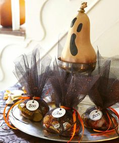 Give dearly departing guests a sneaky send-off with tulle-shrouded favors that conceal foil-wrapped candies and more. Cut the semi-sheer, glitter-flecked fabric into approximately 7-inch squares. Fill with seasonal sweets and tie with ribbon, adding stationery store tags with a message penned in script. A spooky butternut squash (spray-painted copper) with a classic Scream face, overlooks them all.  - GoodHousekeeping.com