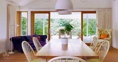 Offener Wohn-, Ess-, Kochbereich mit direktem Zugang zum überdachten Terrassenbereich – Baufritz Landhaus Hauck