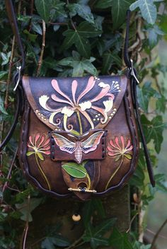 elaborately hand carved honeysuckle and hawk moth on a little mid-brown bag
