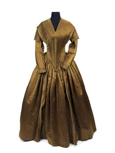 An 1840s bronze silk satin day dress The bodice sharply pleated into a deep pointed waist, a v-neckline and long slightly shaped sleeves with decorative capped over-sleeves, trimmed with silk braid and satin covered buttons, the skirt tightly pleated into the waist, with vertical bands trimmed with braid.