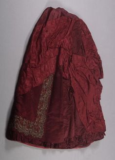 Skirt from dress (bodice and skirt) Date: 1880–1890 Media: Silk Satin And Damask, Metallic Lace Country: United States Accession Number: 1983.60.1b Skirt is draped to one hip, satin panel. Made for a bustle. Trimmed with an applique band of embroidered and beaded velvet to match bodice.