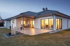 Bungalow Walmdach 130. Der klassische Winkelbungalow überzeugt durch klassische Formen. Die schwarz-weiße Fassade wirkt zeitlos und elegant, im Innenbereich herrschen Grau- und Brauntöne in starken Hell- und Dunkelkontrasten vor. Die geradlinigen Möbel wirken modern, Farbakzente, vereinzelte Muster, Holzmöbel und Pflanzen sorgen für Gemütlichkeit. Die im Winkel liegende Terrasse bietet Raum für Grillabende, Kaffeekränzchen oder Sonnenbäder.  Gesamtwohnfläche 130 m²